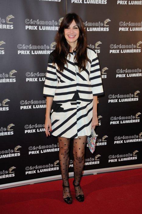 Helena Noguerra joue avec les motifs de sa robe et de ses collants, sur le tapis rouge de la Cérémonie Des Prix Lumières en 2015.